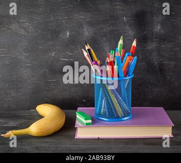 Banane jaune, bleu verre papeterie avec multi-couleur des crayons et des stylos en bois, sur l'arrière-plan d'un tableau noir vide, le retour à l'école Banque D'Images