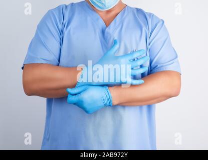 Médecin homme en uniforme bleu met ses mains Gants latex stériles blanc avant une chirurgie, fond blanc. Banque D'Images