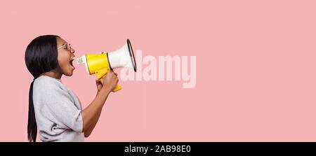 Jeune femme criant dans un mégaphone sur fond rose