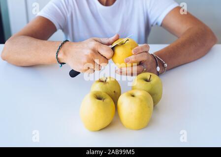 Close up of mother l'épluchage des pommes vertes sur la table.