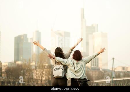 Retour de deux femmes à la recherche à l'horizon de ville, bras levés, à Frankfurt am Main, Allemagne