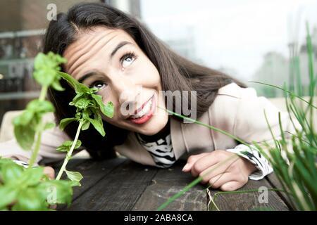 Femme curieuse à côté du basilic et ciboulette plantes Banque D'Images