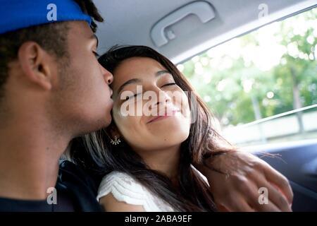 Jeune couple assis ensemble dans le siège arrière de voiture. Banque D'Images