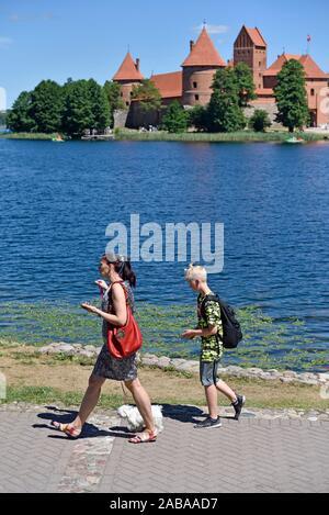 Les marcheurs par le lac Galve avec le Château de Trakai en arrière-plan, de la Lituanie, de l'Europe. Banque D'Images
