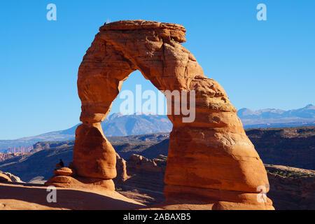 Les deux personnes et les oiseaux à profiter de la vue de la Delicate Arch sur une belle journée d'automne. Banque D'Images