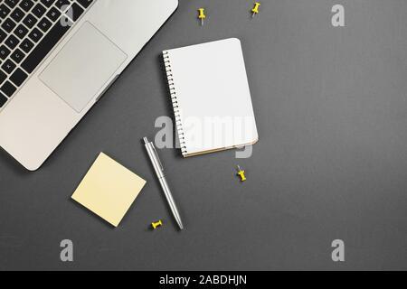 Planification financière mise à plat table top image malpropre de remue-méninges avec les fournitures de bureau, stylo, bloc-notes, ordinateur portable sur fond gris. Vue de dessus, copy space Banque D'Images