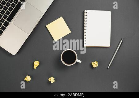 Planification financière mise à plat table top image malpropre de remue-méninges avec les fournitures de bureau, stylo, bloc-notes, ordinateur portable, tasse de café sur fond gris. Vue d'en haut Banque D'Images