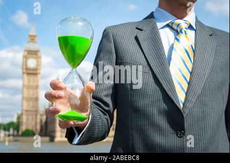 British businessman holding a green hourglass changement climatique devant le Big Ben et les chambres du Parlement de Westminster à Londres, Royaume-Uni Banque D'Images