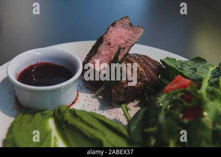 Moyen juteux steak saignant sur la plaque blanche dans le restaurant. La viande servie avec salade épinards purée et sauce aux canneberges. Banque D'Images