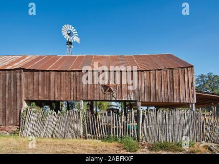 Une ancienne grange en bois avec un maigre à toit de tôle rouillée, et l'étoile du Texas accroché sur son mur sur une rue à Round Top, Texas. Banque D'Images