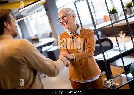 Reconnaissant senior businesswoman femme chef tenir main de meilleur employé, agiter les mains au chaud en accueillant espace de coworking Banque D'Images