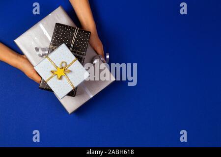 Mains tenant présente enveloppés dans du papier cadeau sur fond bleu marine. Noël, Nouvel An, vacances concept Banque D'Images