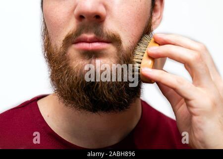 Gros plan du bel homme brossant sa barbe isolé sur fond blanc Banque D'Images