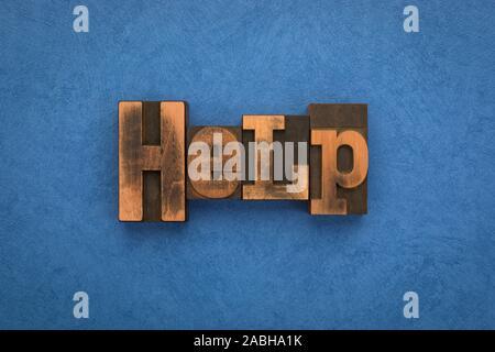 L'aide, seul mot écrit avec la typographie vintage blocks sur fond bleu texturé. Banque D'Images