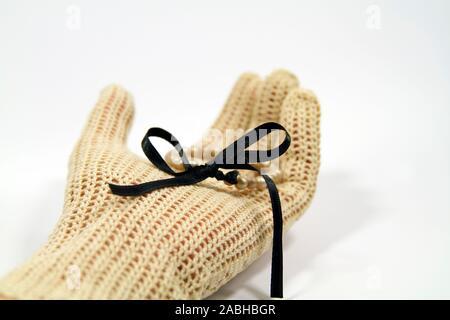 La main avec des gants en crochet vintage bracelet pearl holding avec ruban de satin noir Banque D'Images