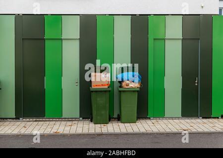 Trop rempli deux poubelles sur un mur rayé Banque D'Images