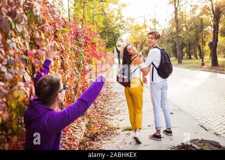 Happy young couple salutation et brandissant leur ami dans la rue Banque D'Images