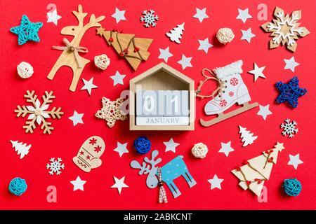 Vue de dessus du calendrier en bois, maison de jouets et des décorations de Noël fond rouge. La première de janvier. Nouveau concept de temps de l'année.