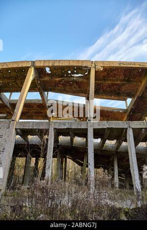 La structure industrielle de béton ruinée en forêt au coucher du soleil. Banque D'Images