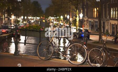 Une photo de nuit d'un vélo enchaîné à un pont sur un canal à Amsterdam aux Pays-Bas