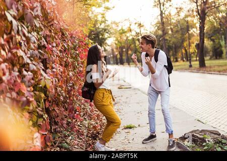 Jeune couple excité ou fêter la réussite d'amis raising arms, sur la rue Banque D'Images