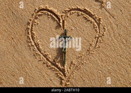 Forme de coeur dessiné dans le sable avec croix chrétienne. Banque D'Images