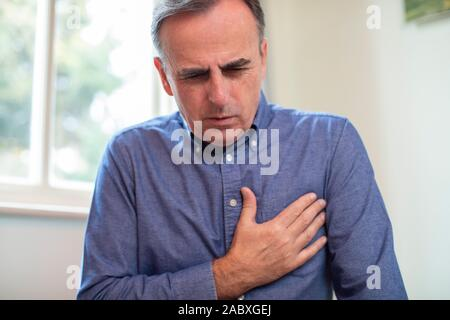 Homme mûr souffrant des douleurs de poitrine et la crise cardiaque à la maison Banque D'Images