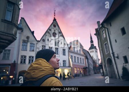 Jeune homme en manteau d'hiver marchant dans la rue historique à moody le coucher du soleil. Vieille ville de Tallinn, Estonie. Banque D'Images