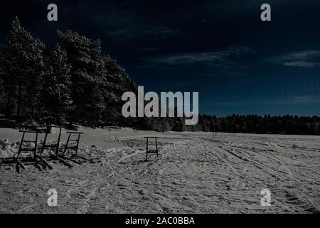 La Finlande, Inari - Janvier 2019: paysage d'hiver lune lapon avec forêt et lac sur ciel bleu avec des nuages plein couverts super pleine lune Banque D'Images