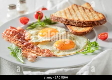 Petit-déjeuner frais avec des oeufs, bacon et tomates Banque D'Images
