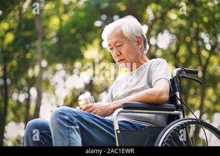 Asian vieil homme assis dans un fauteuil roulant, la tête en bas, à la triste et déprimé Banque D'Images