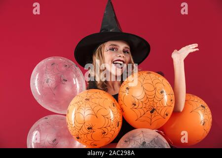 Happy little girl wearing costume Halloween isolés sur fond rouge, holding bunch of balloons Banque D'Images