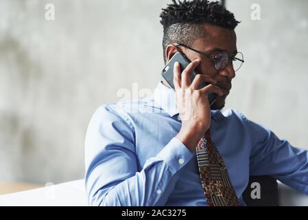 La photo en gros plan de l'homme noir élégant attrayant en fonction téléphone parler avoir traiter