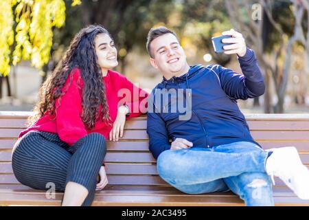 Deux amis de prendre un sur un banc de parc selfies Banque D'Images