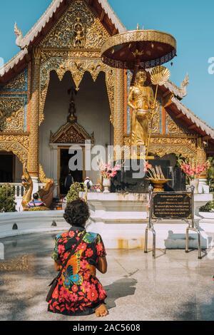 Thaï non identifié femme qui prie en face de Wat Phra Singh temple à Chiang Mai, Thaïlande. Banque D'Images