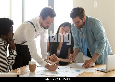 Employés multiraciale ne l'analyse statistique des données de l'examen des tableaux financiers Banque D'Images
