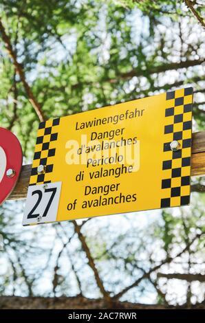 Tourisme jaune avertit signe d'avalanches en quatre langues différentes. Avertissement en allemand, français, italien et anglais. Signe de l'information pour les touristes dans les Alpes suisses.