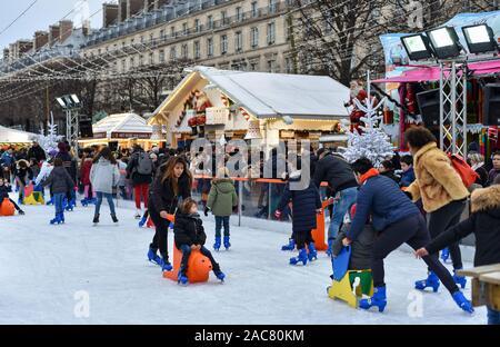 PARIS, FRANCE - 30 NOVEMBRE 2019: les gens s'amuser sur une patinoire en plein air dans le marché de Noël au Jardin des Tuileries. Banque D'Images