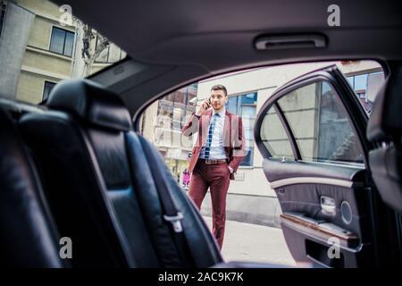 Voiture de la porte ouverte et un homme tout en parlant sur mobile outdoor Banque D'Images