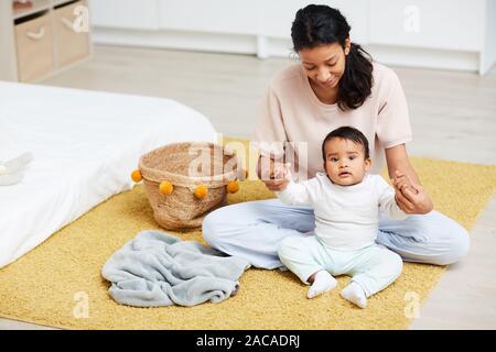 Les jeunes professionnels mère assise sur le sol avec son bébé qu'elle tenait la main et l'aider à s'asseoir Banque D'Images