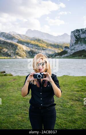 Une belle femme de race blanche avec des vêtements décontractés prend des photos avec un appareil photo dans un paysage montagneux avec lake