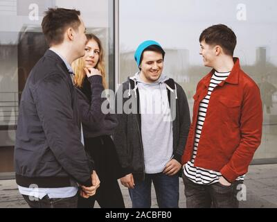 Groupe de quatre jeunes amis adolescents parler rire et s'amuser ensemble - candid de vraies personnes Banque D'Images