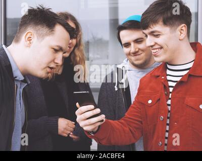 Jeune homme montrant quelque chose de drôle sur son smartphone à un groupe d'amis adolescents, focus on hand holding mobile phone, filtre mat Banque D'Images