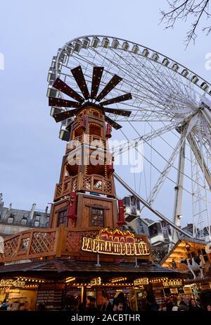 PARIS, FRANCE - 30 NOVEMBRE 2019: tour en bois géant et une grande roue à l'arrière-plan dans le marché de Noël au Jardin des Tuileries à Paris. Banque D'Images