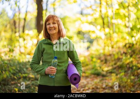 Happy senior femme est prête pour l'exercice en parc.