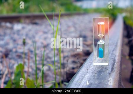 Hourglass transparent avec sable bleu l'article sur l'ancien chemin de fer rouillé avec effet de lumière, l'heure concept Banque D'Images