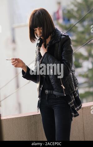 Portrait d'une jeune femme avec veste rock cigarette.