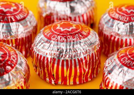 Un certain nombre de chocolat au lait de la marque Tunnock gâteaux thé tourné sur un fond jaune. Banque D'Images