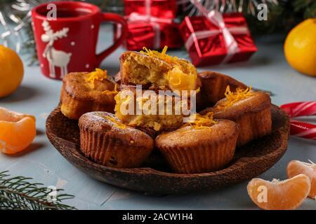 Muffin maison avec la mandarine, saupoudré de sucre en poudre est situé sur le Nouvel An ou Noël fond bleu clair Banque D'Images