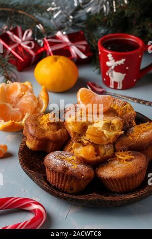 Muffin maison avec la mandarine, saupoudré de sucre en poudre est situé sur le Nouvel An ou Noël fond bleu clair, gros plan Banque D'Images